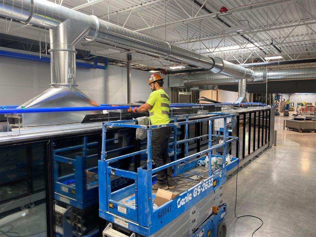 Workers installing refrigeration equipment